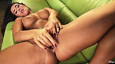 Delicious moll lies on the green sofa and tries to make her hole wider