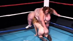 A midget and a fat bitch are in the ring eating and toys pussy