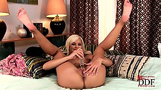 With the help of a glass dildo, a slender blonde drives her sweet cunt to climax