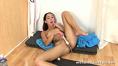 She slips the vibrating sex toy in her sweet spot on the gym floor